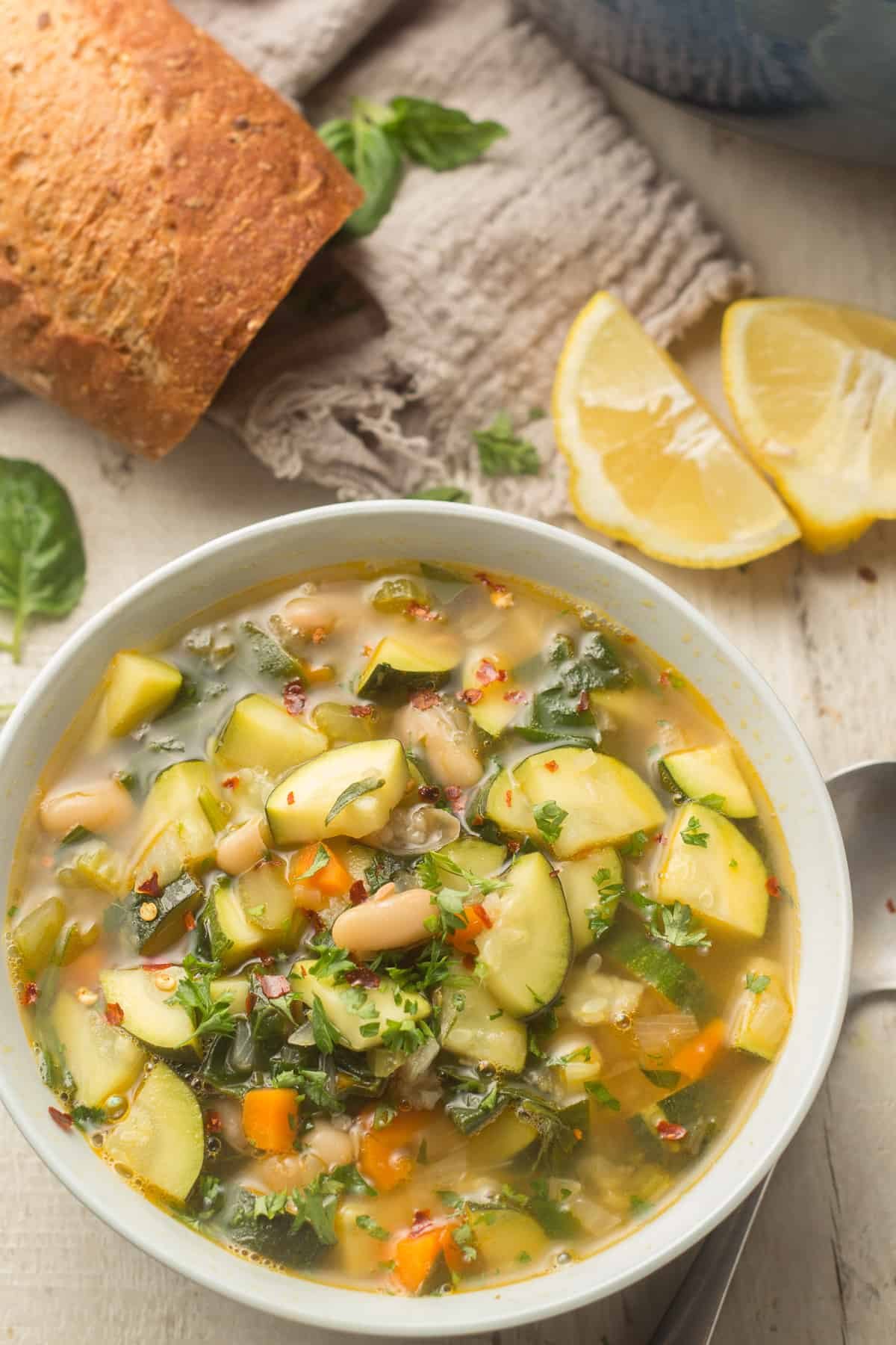 Bowl of Zucchini Soup with Baguette and Lemon Wedges in the Background