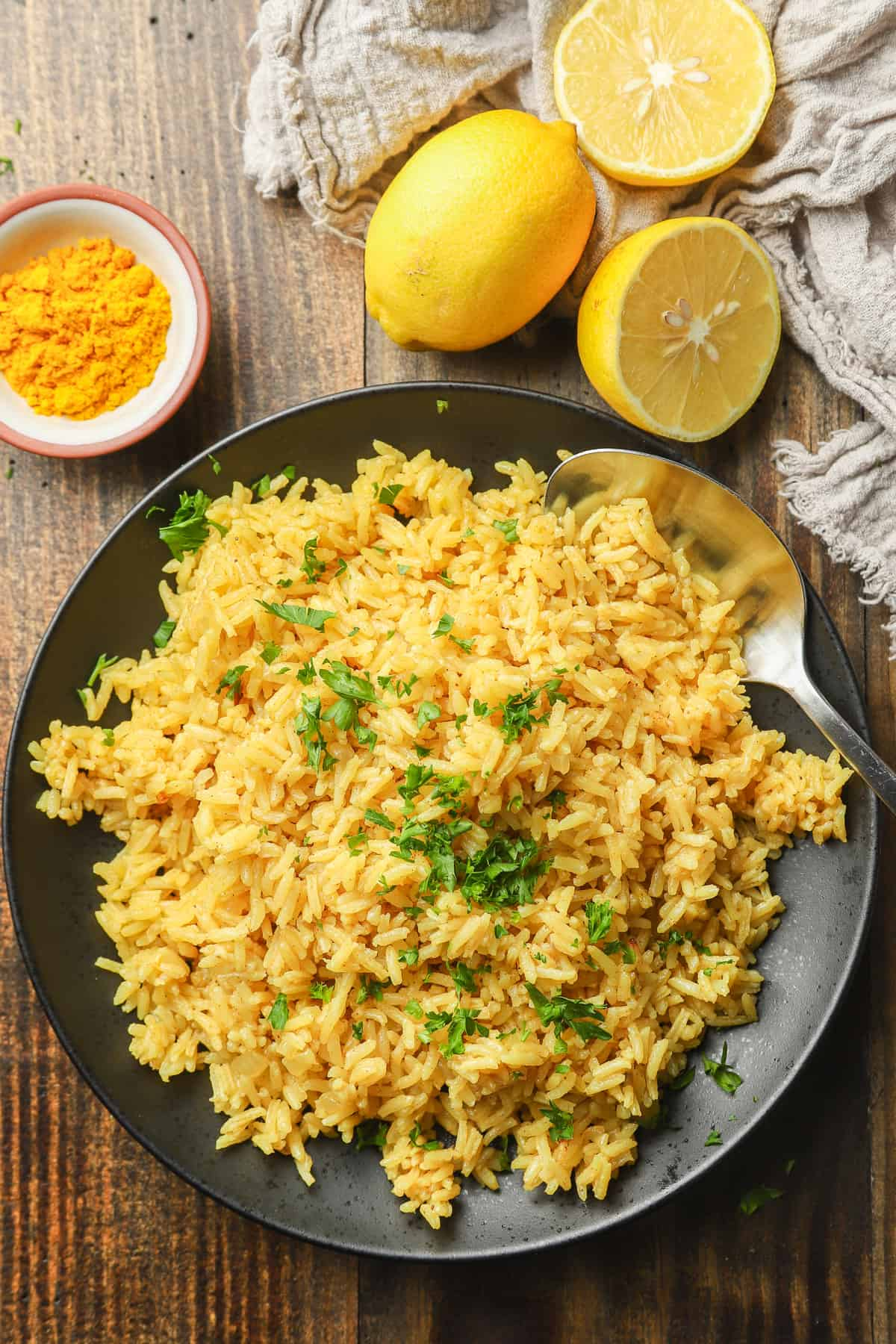 Wooden Table Set with a Plate of Turmeric Rice, Lemons, and Dish of Turmeric