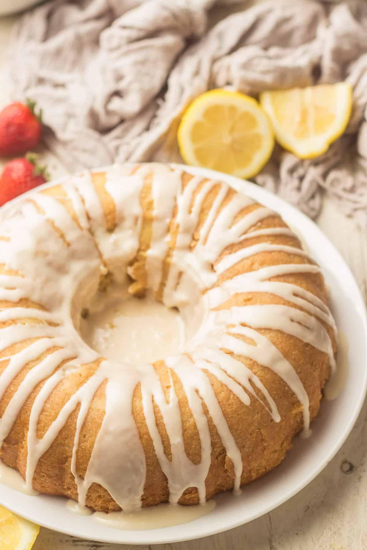 Vegan Lemon Bundt Cake on a dish with Napkin, Strawberries, and Lemon Slices in the Background