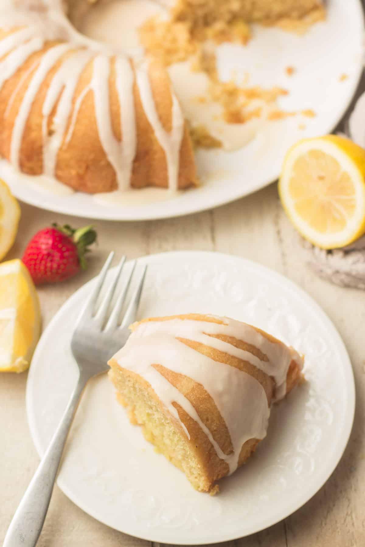 Table Set with Vegan Lemon Cake on a Dish, Lemon Slices, Strawberries, and a Slice of Vegan Lemon Cake on a Plate