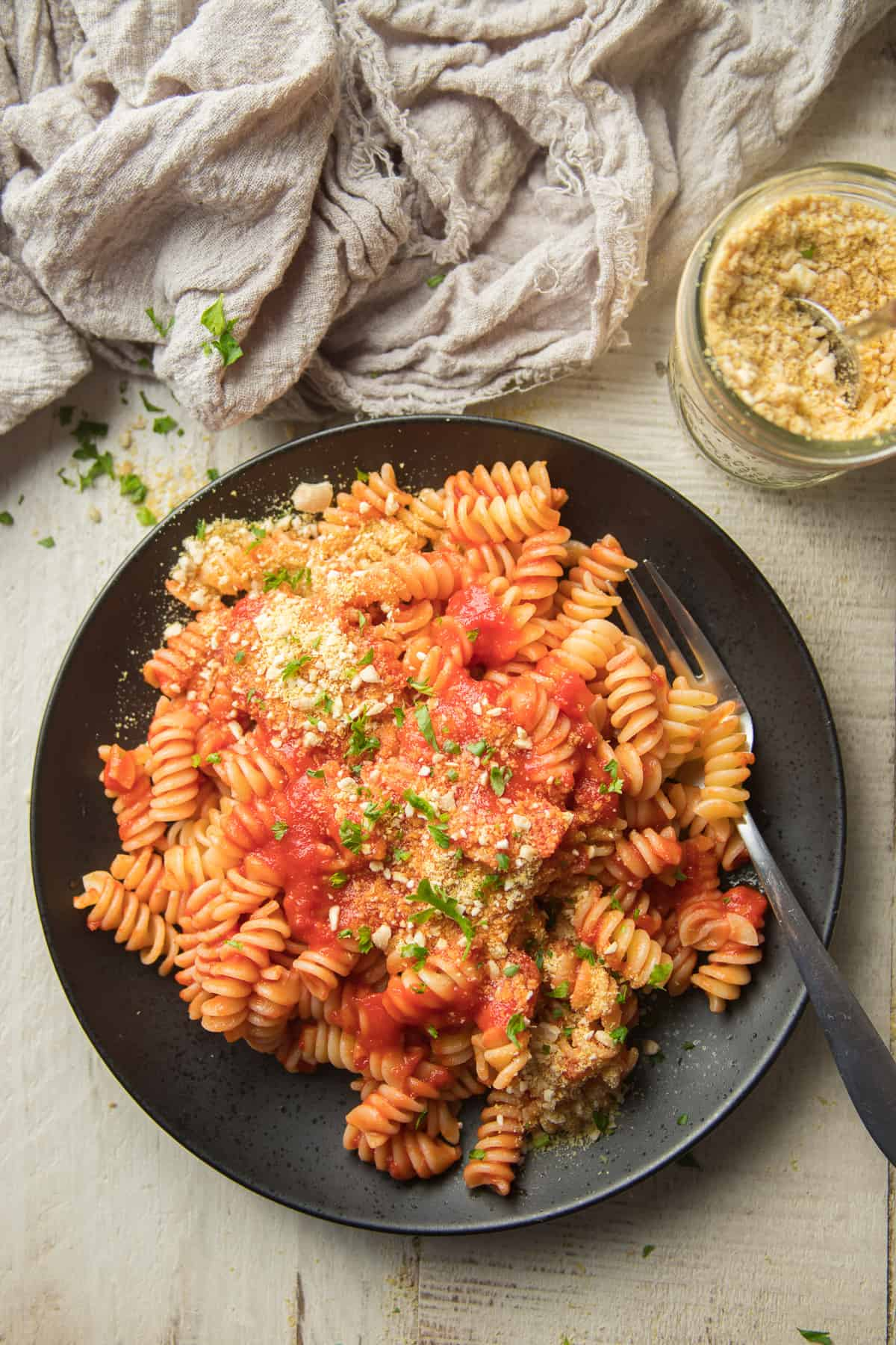 Plate of Rotini Pasta Topped with Tomato Sauce and Vegan Parmesan Cheese