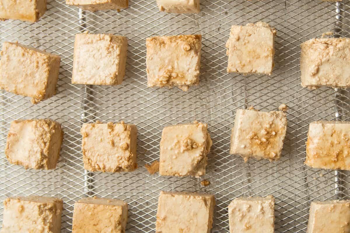 Tofu Pieces Coated with Seasonings in Air Fryer Basket