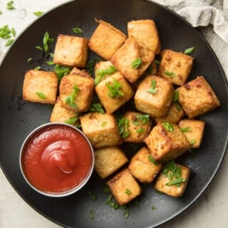 Plate of Air Fryer Tofu with Chives on Top and Sauce on the Side