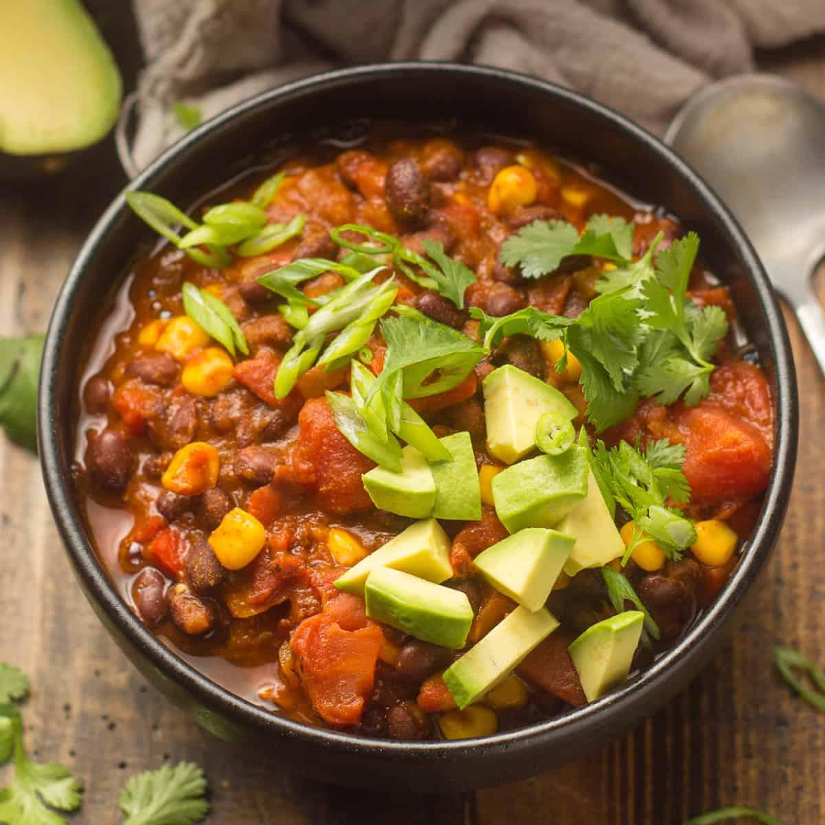 Bowl of Black Bean Chili Topped with Avocado, Scallions and Cilantro