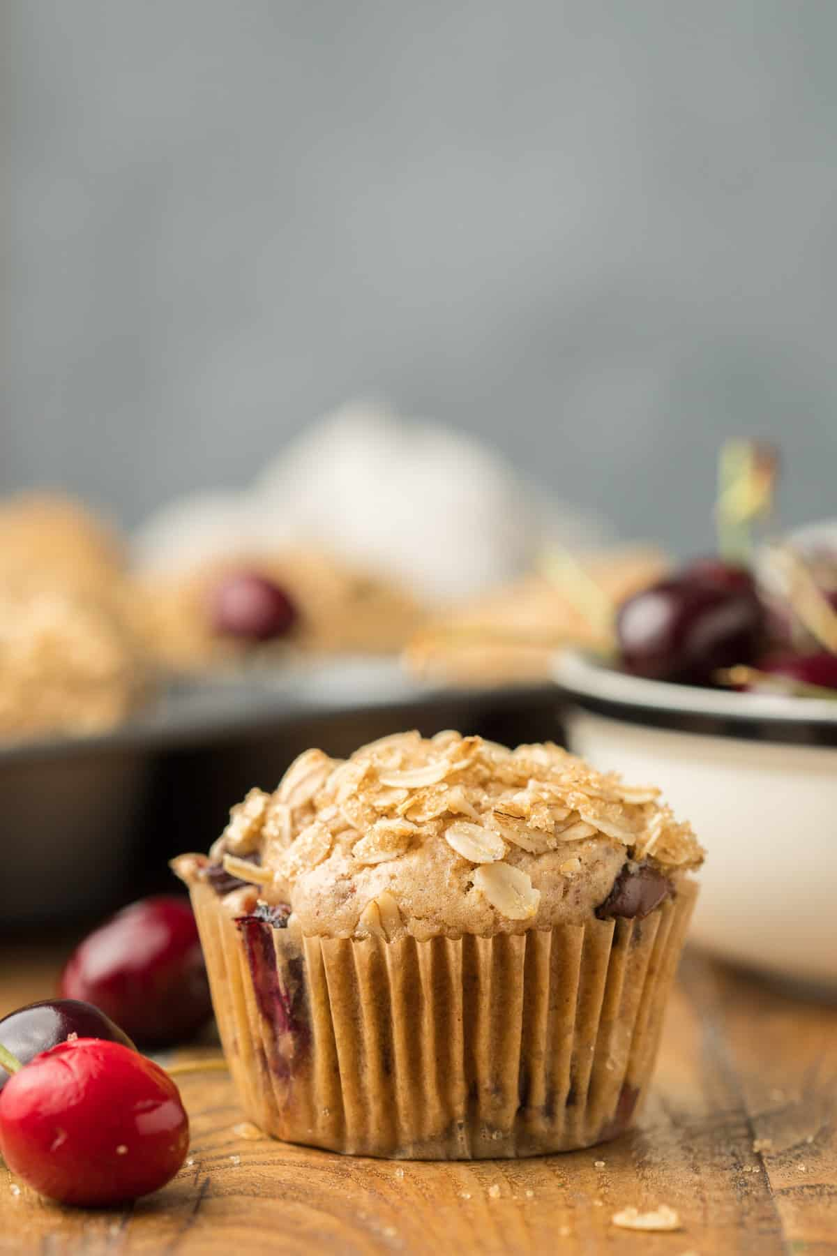 Close Up of a Vegan Cherry Muffin with Bowl of Cherries in the Background