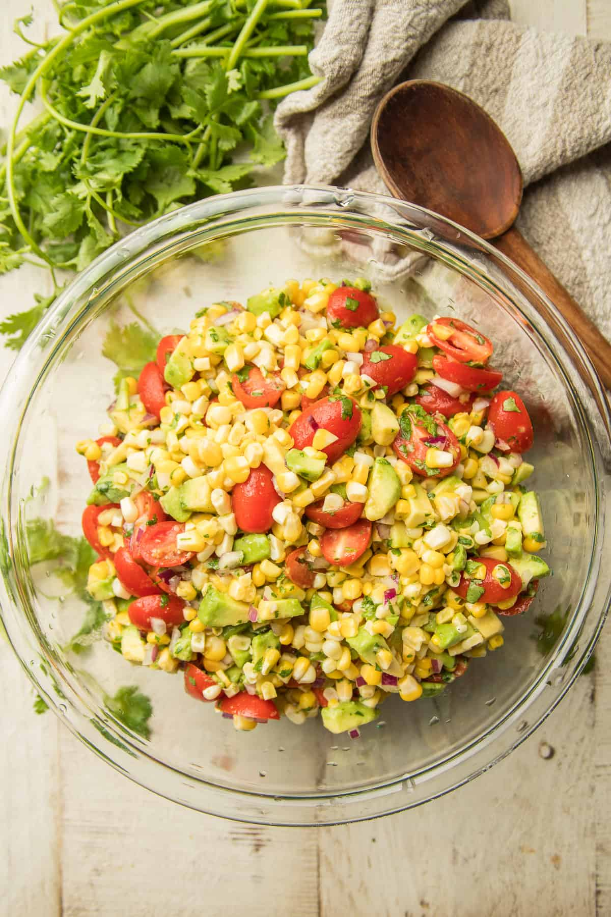 White Wooden Surface Set with Bunch of Cilantro, Bowl of Avocado Corn Salad, and Wooden Spoon