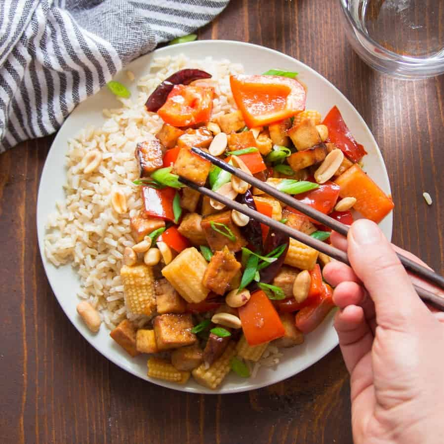 Hand Picking Up a Piece of Kung Pao Tofu with Chopsticks