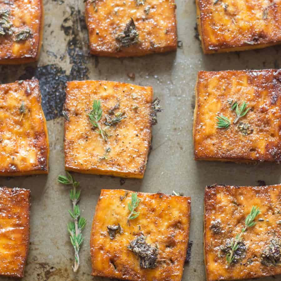 Lemon & Herb Baked Tofu Pieces on a baking Sheet with Herbs