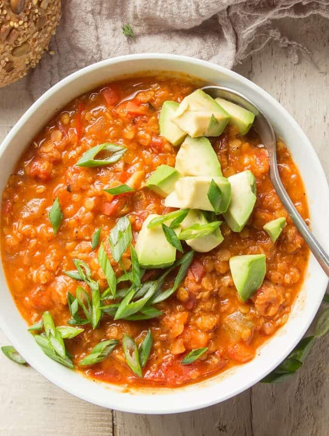 Bowl of Red Lentil Chili Topped with Scallions and Avocado