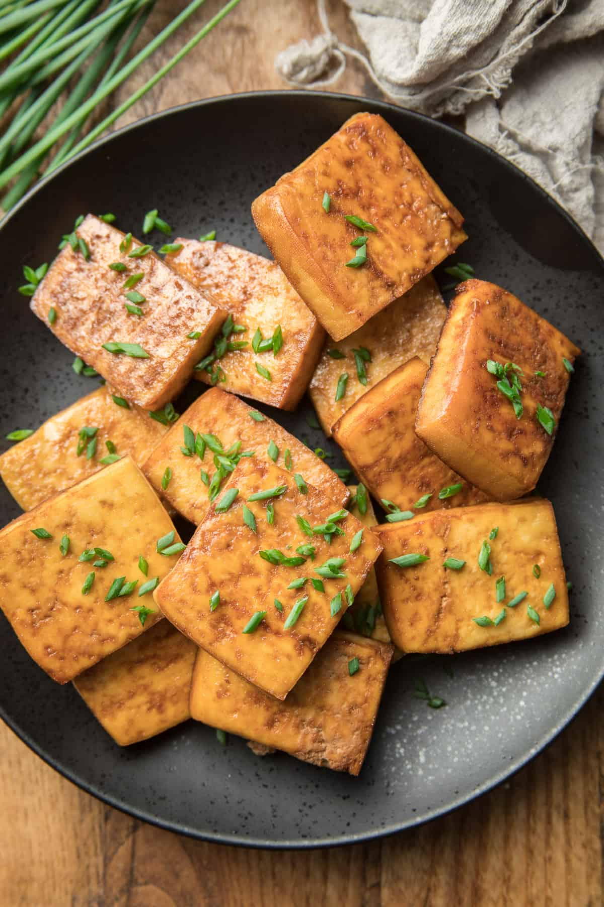 Plate of Smoked Tofu on a Wooden Surface with Chives