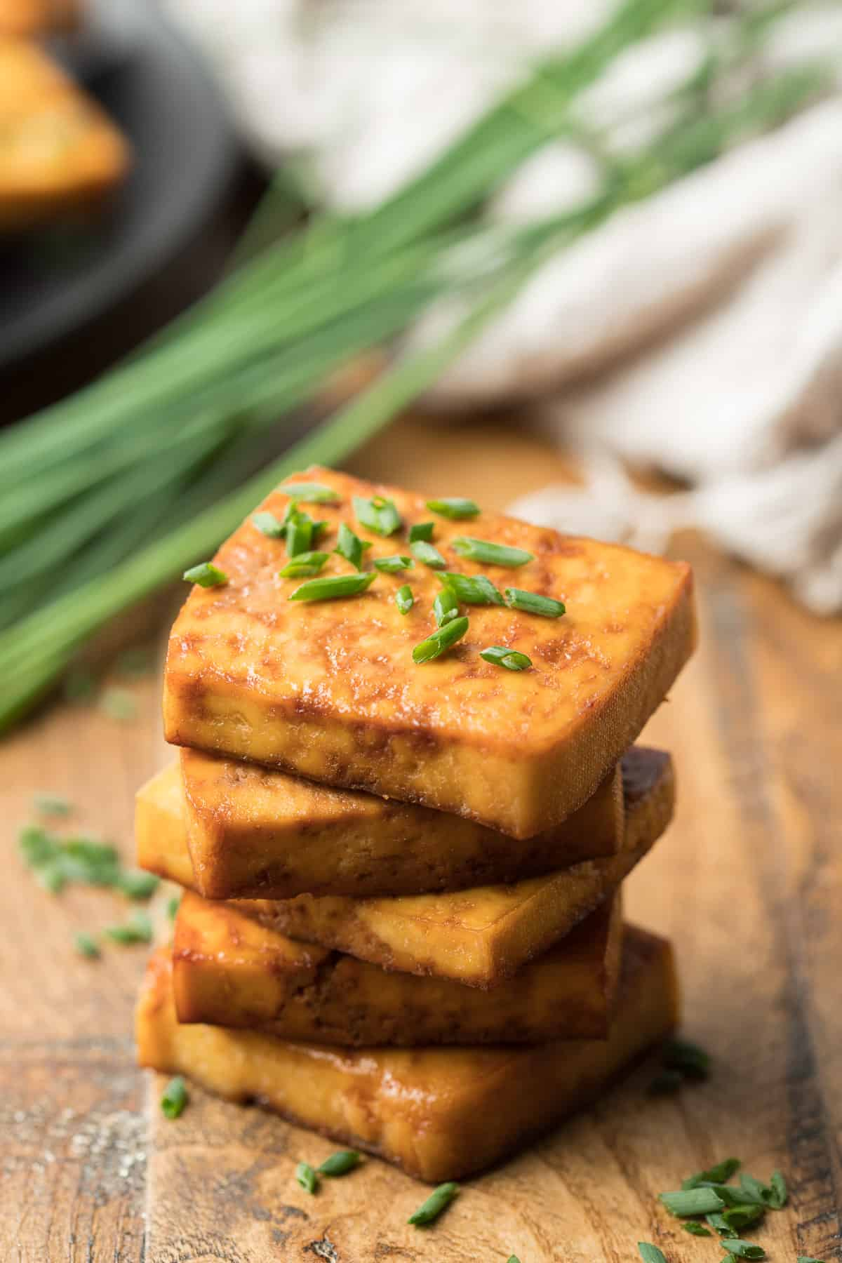Stack of Smoked Tofu with Chives and Skillet in the Background