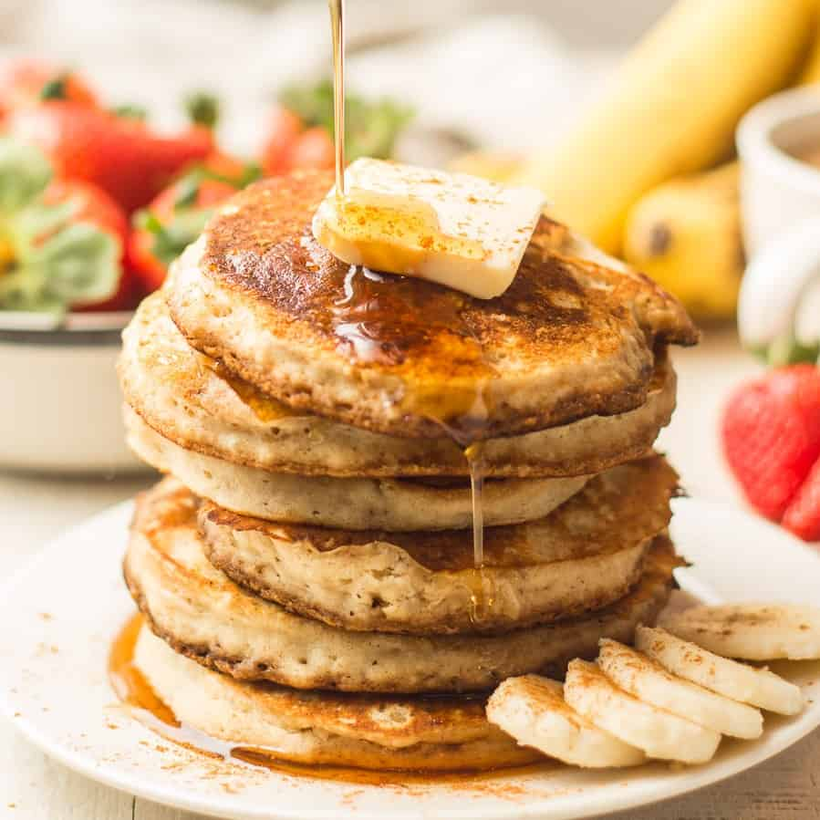 Hand Drizzling Maple Syrup Over a Stack of Vegan Banana Pancakes