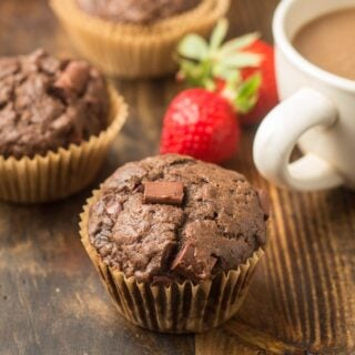 Vegan Double Chocolate Muffins on a Wood Surface with Coffee Cup, Strawberries and Additional Muffins in the Background