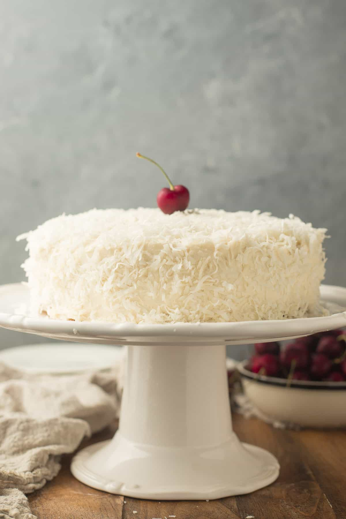 Vegan Coconut Cake on a Cake Dish with a Cherry on Top