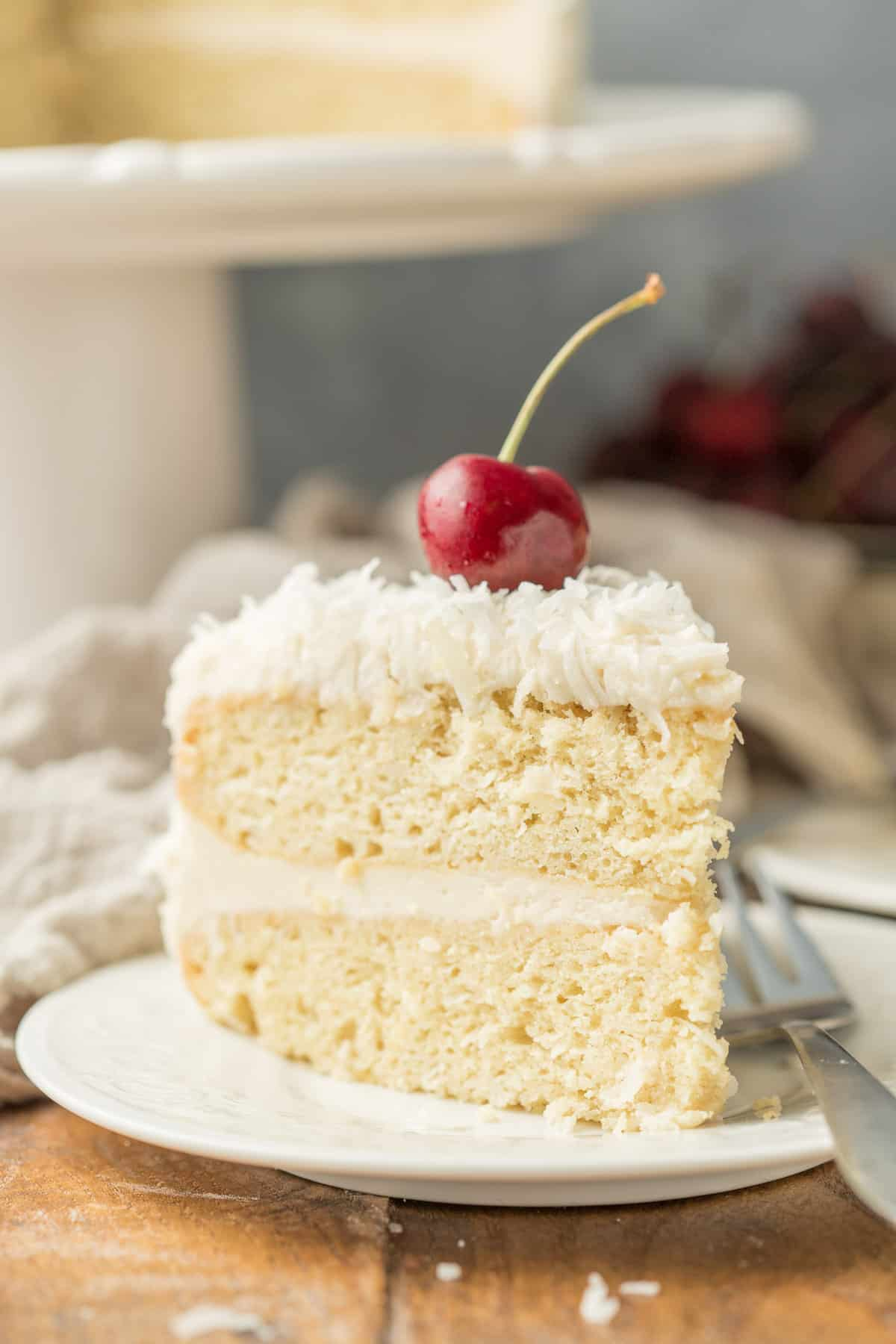 Slice of Vegan Coconut Cake on a Plate with a Cherry on Top