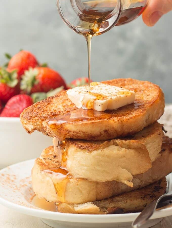 Hand Pouring Maple Syrup Over a Stack of Vegan French Toast