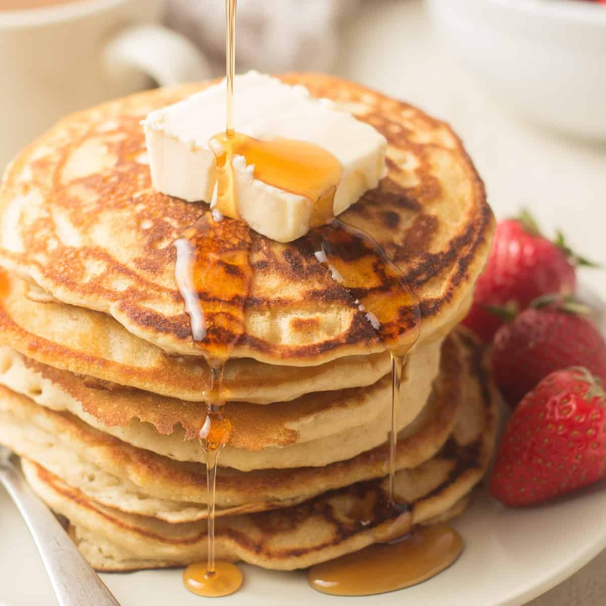 Syrup Being Poured Over a Stack of Vegan Pancakes with Butter and Strawberries
