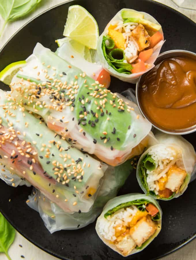 Vegan Summer Rolls Topped with Sesame Seeds and Dish of Peanut Sauce on a Plate