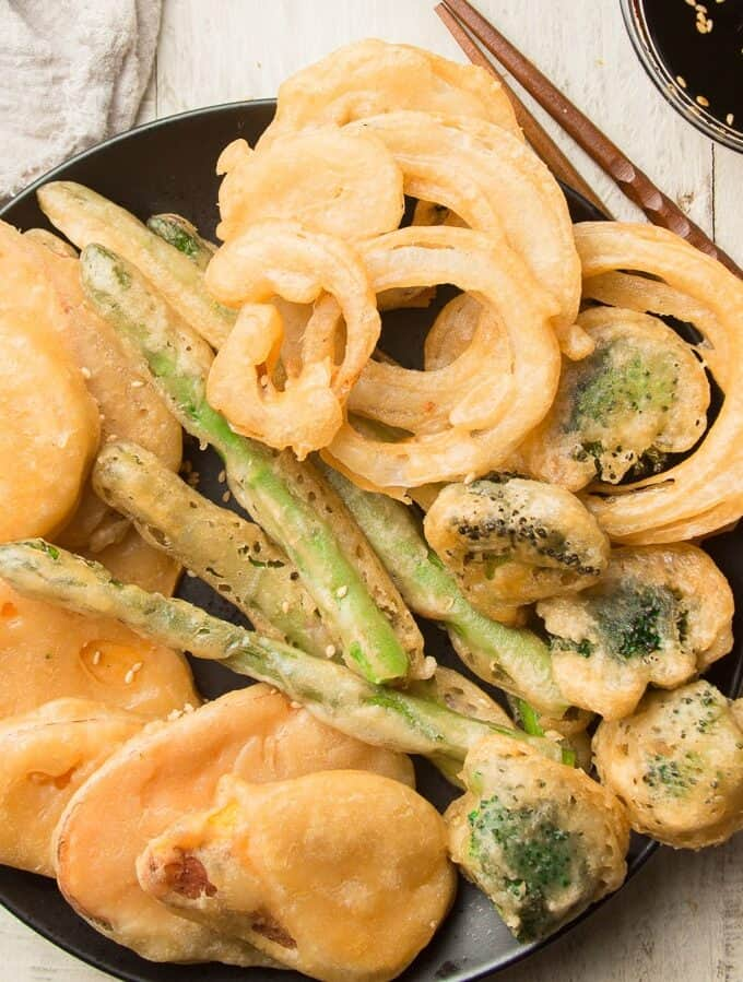 Tempura Vegetables on a Black Plate with Chopsticks and Dipping Sauce on the Side