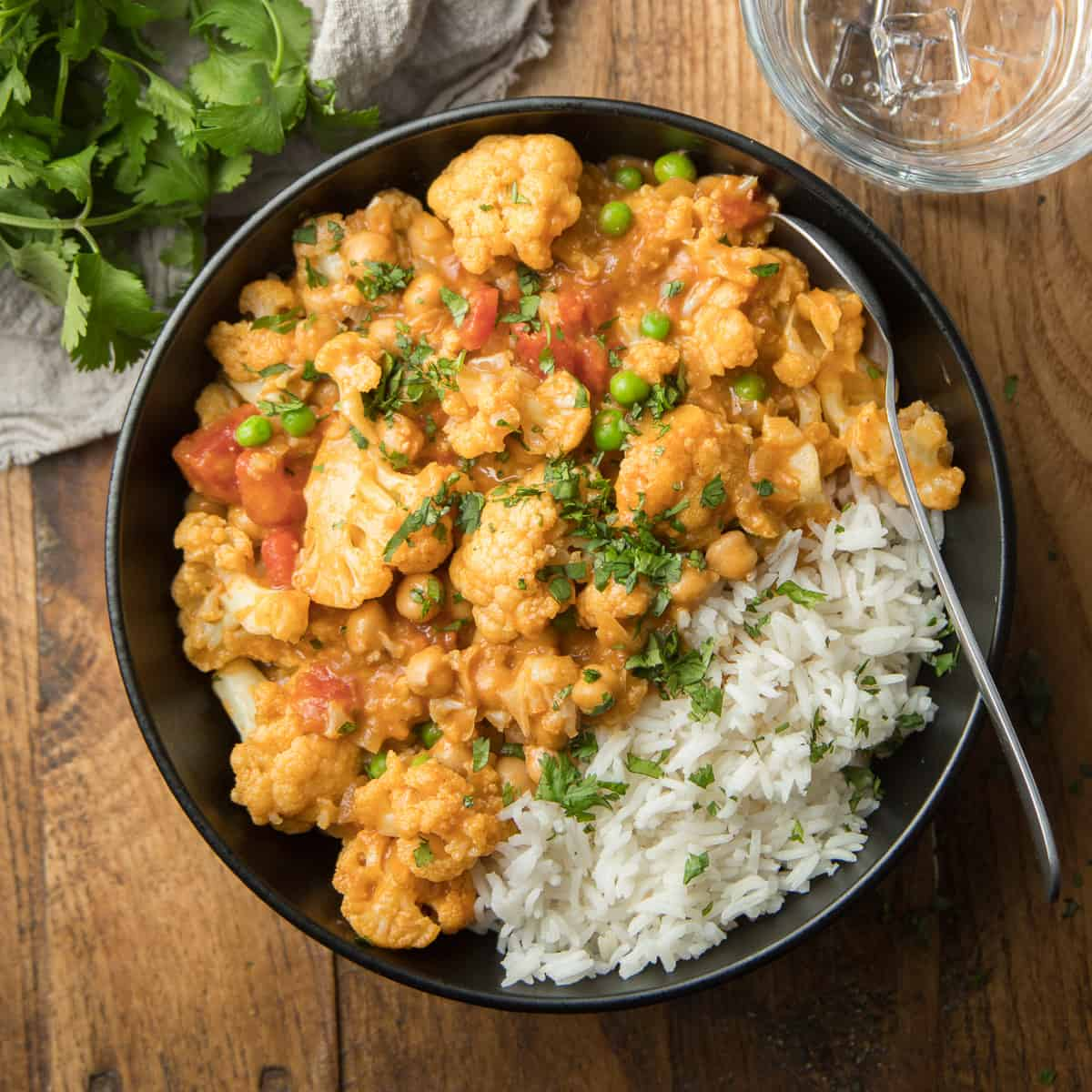 Bowl of Cauliflower Curry and Rice on a Wooden Surface