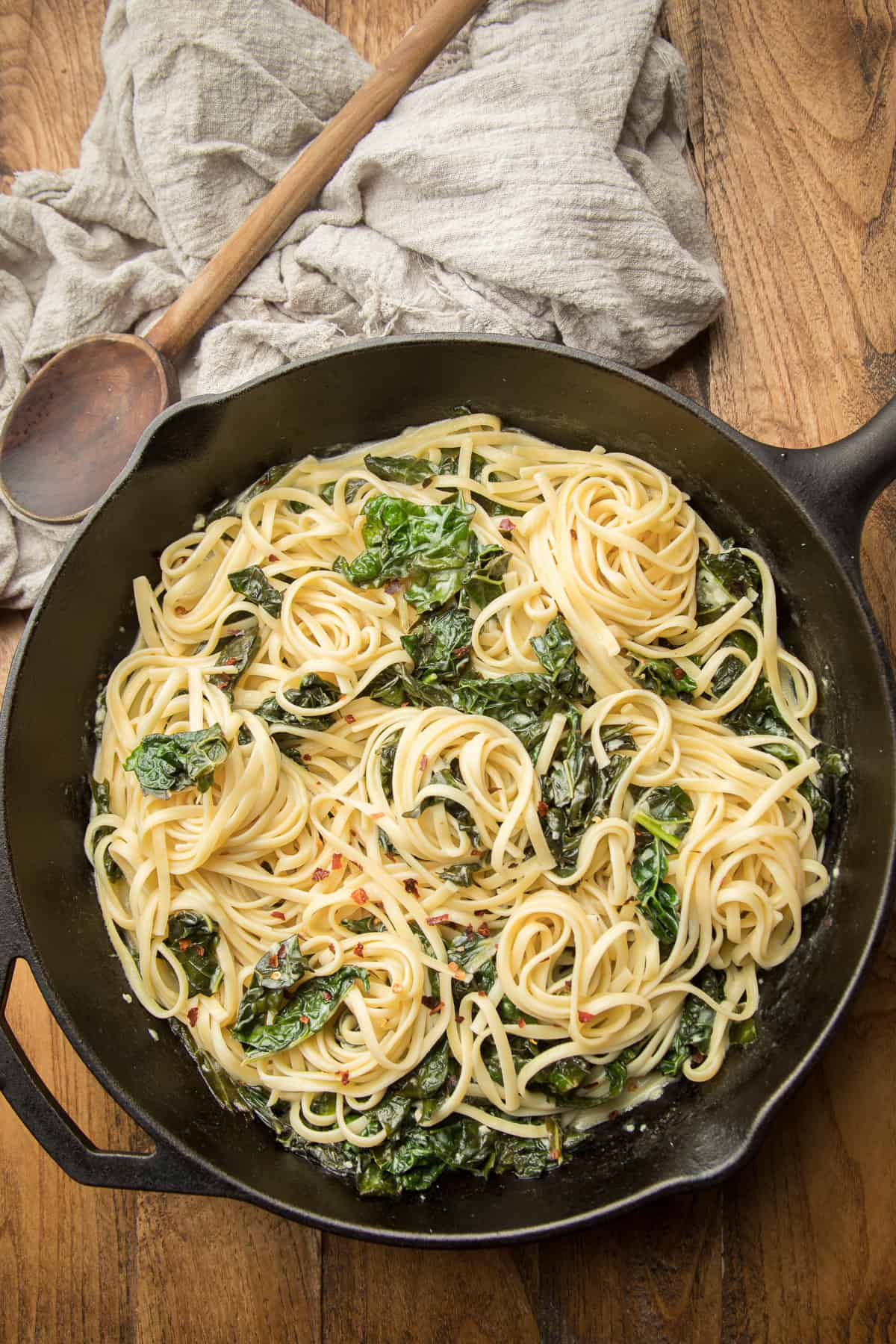 Skillet of Creamy Kale Pasta and Wooden Spoon on a Wooden Surface