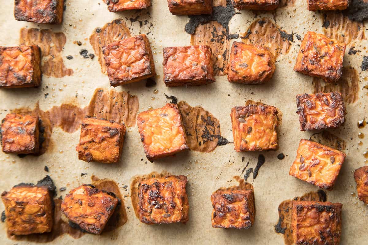 Baked tempeh cubes on parchment paper.