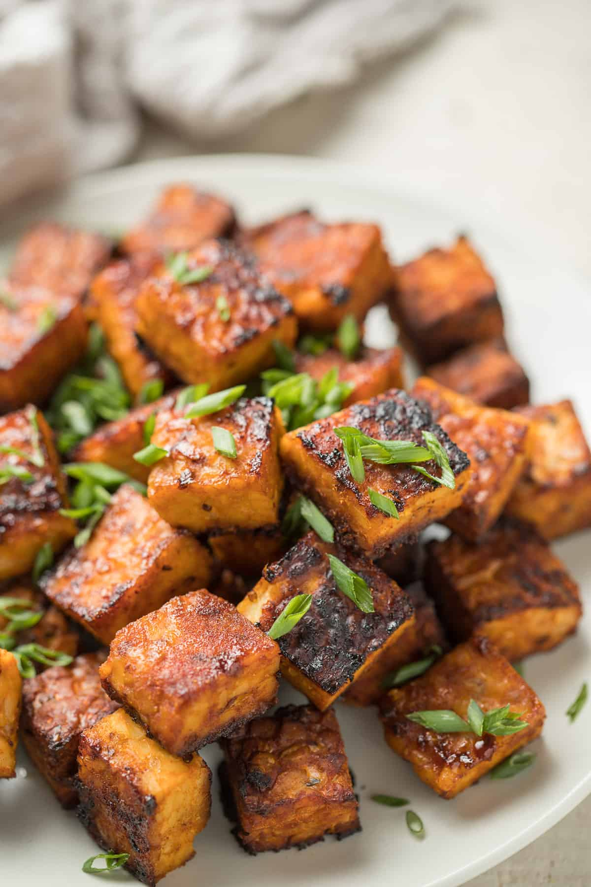 Close up of Smoky Marinated Tempeh on a plate with chives.