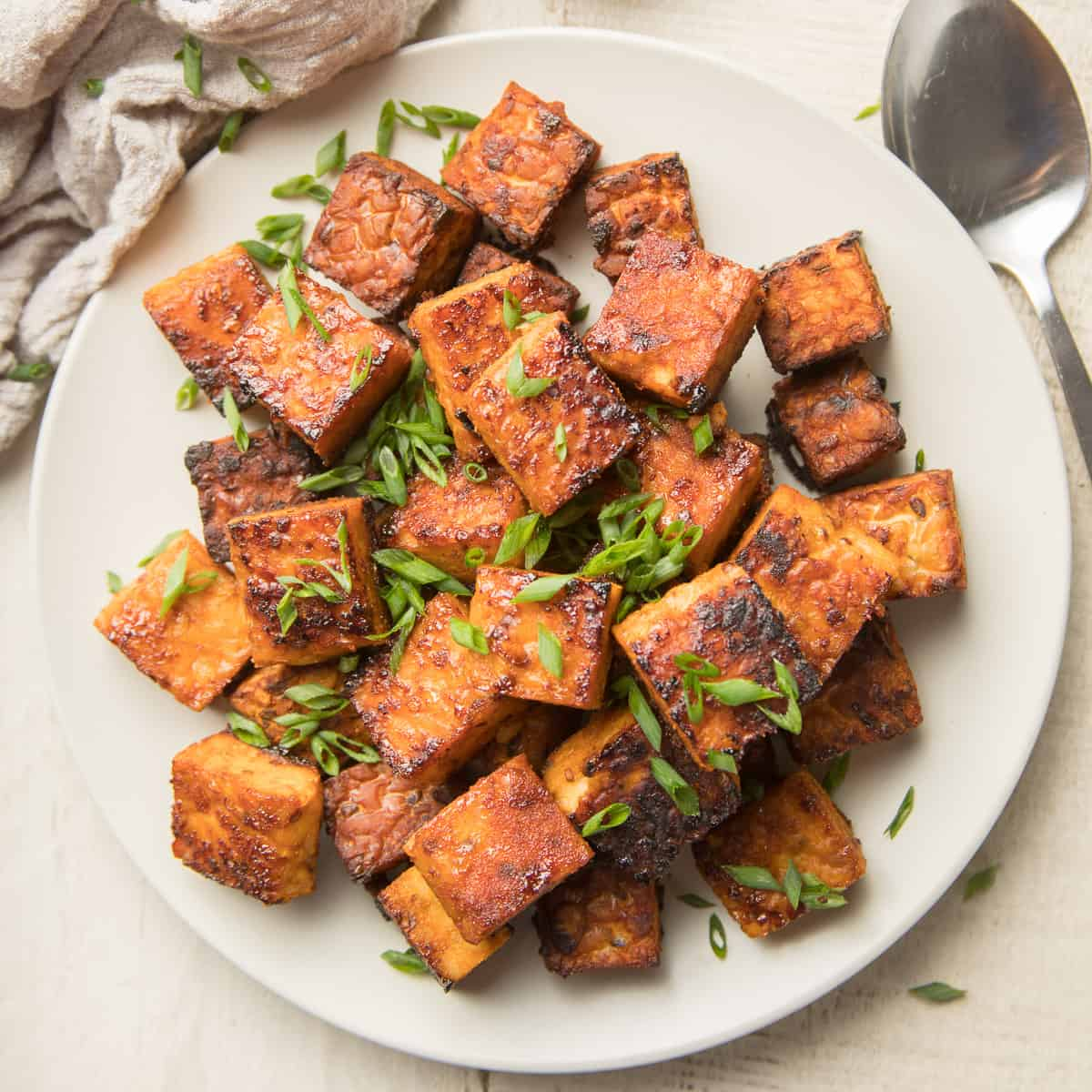 Plate of Smoky Marinated Tempeh with Chives on Top and Spoon on the Side.