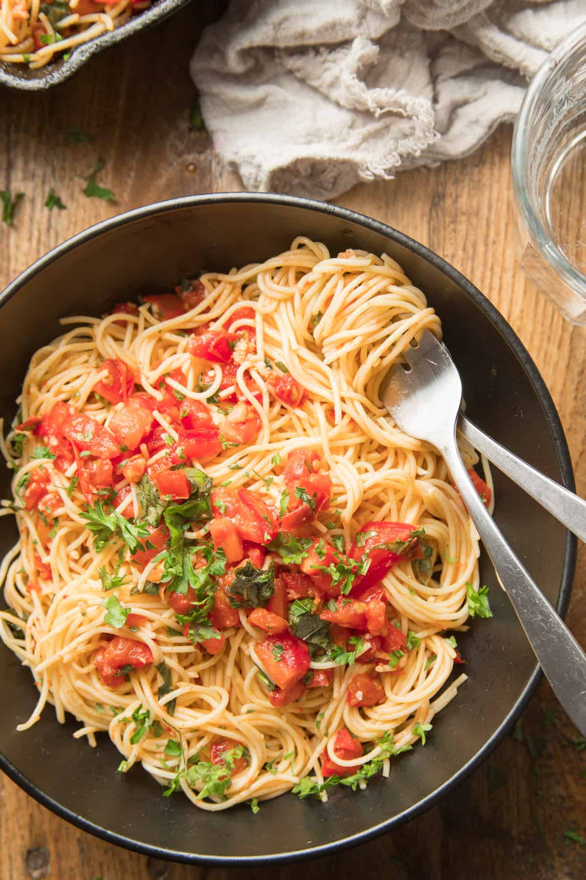 Close Up of a Bowl of Tomato Basil Pasta with Fork and Spoon