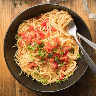 Bowl of Tomato Basil Pasta with Fork and Spoon
