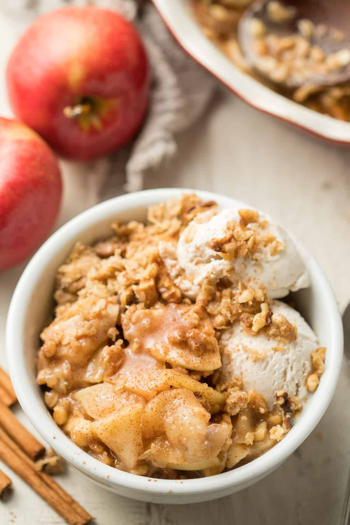 Bowl of Vegan Apple Crisp and Ice Cream with Apples and Baking Dish in the Background