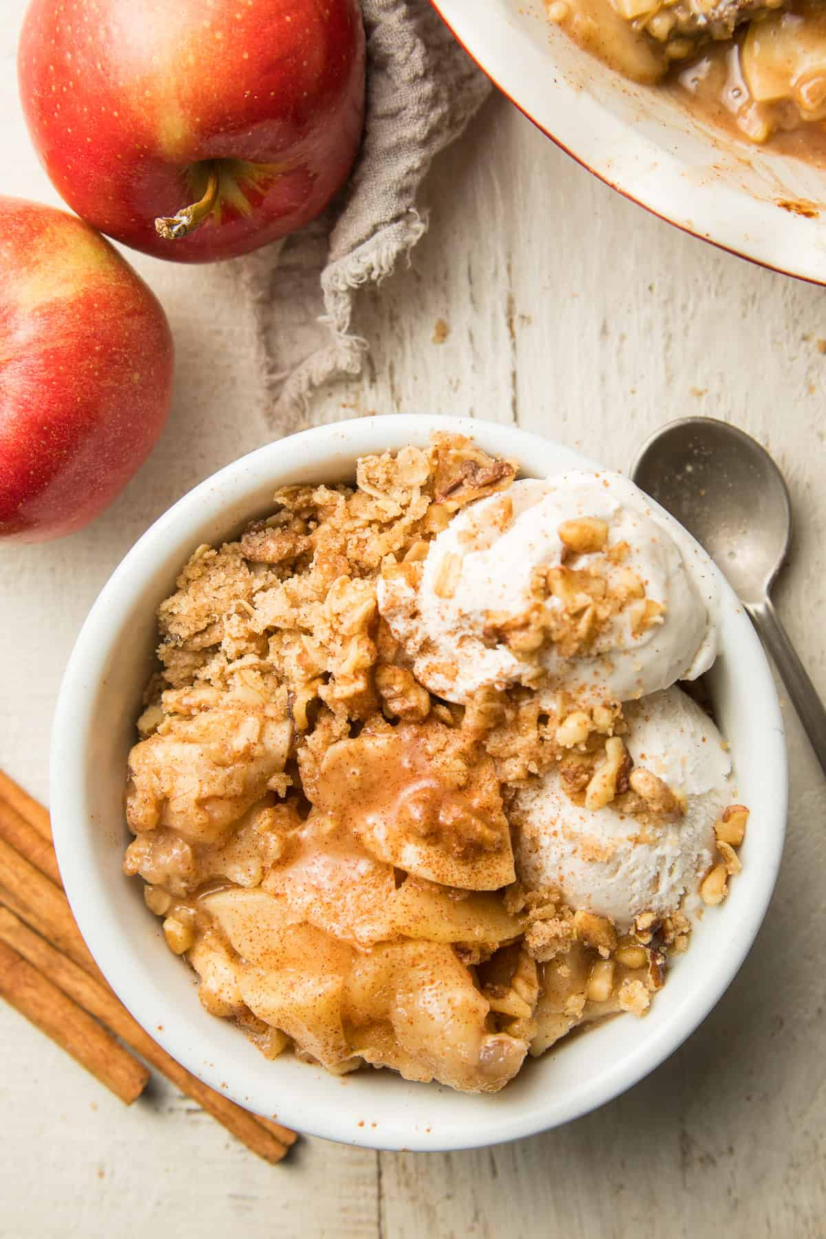White Wooden Surface Set with Apples, Cinnamon Sticks, Baking Dish, and Bowl of Vegan Apple Crisp with Ice Cream