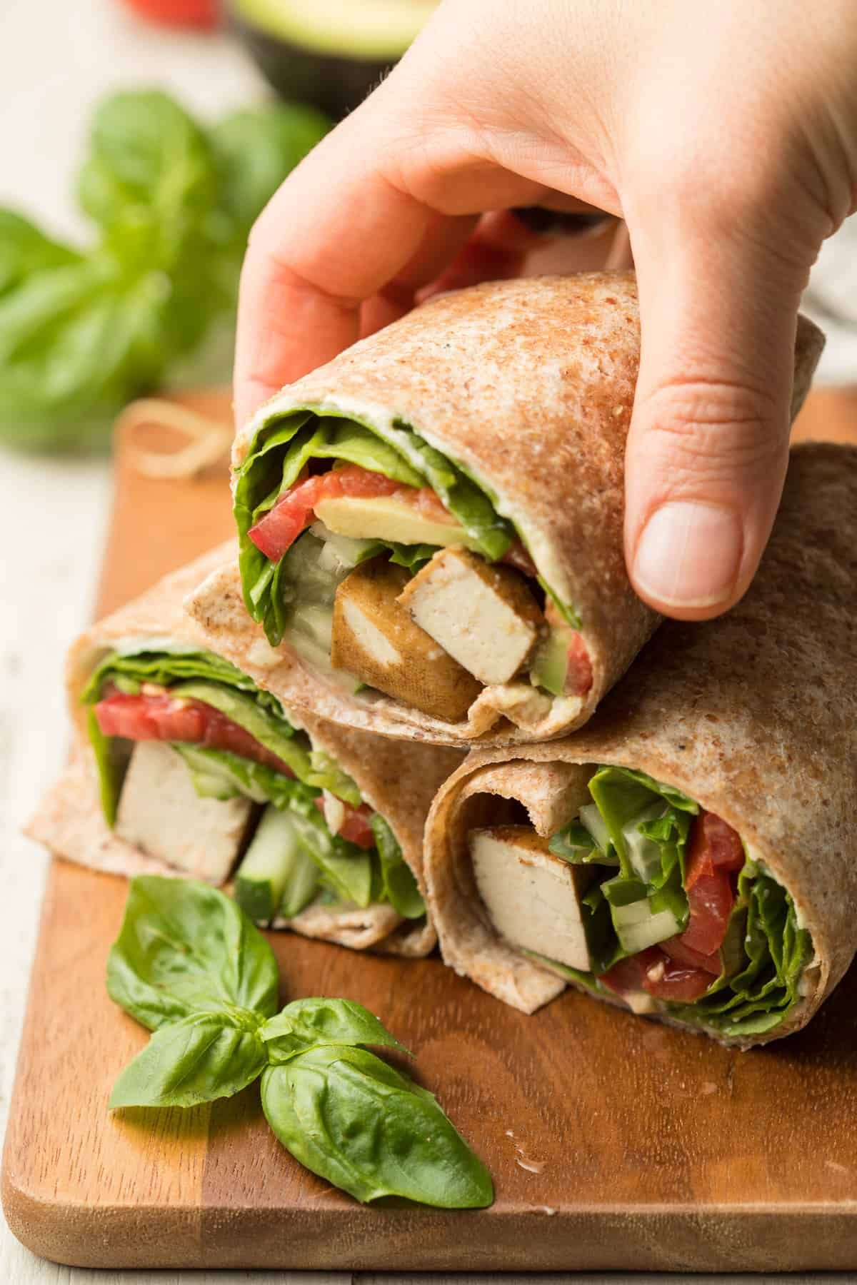 Hand Grabbing a Vegan Wrap Half from a Stack