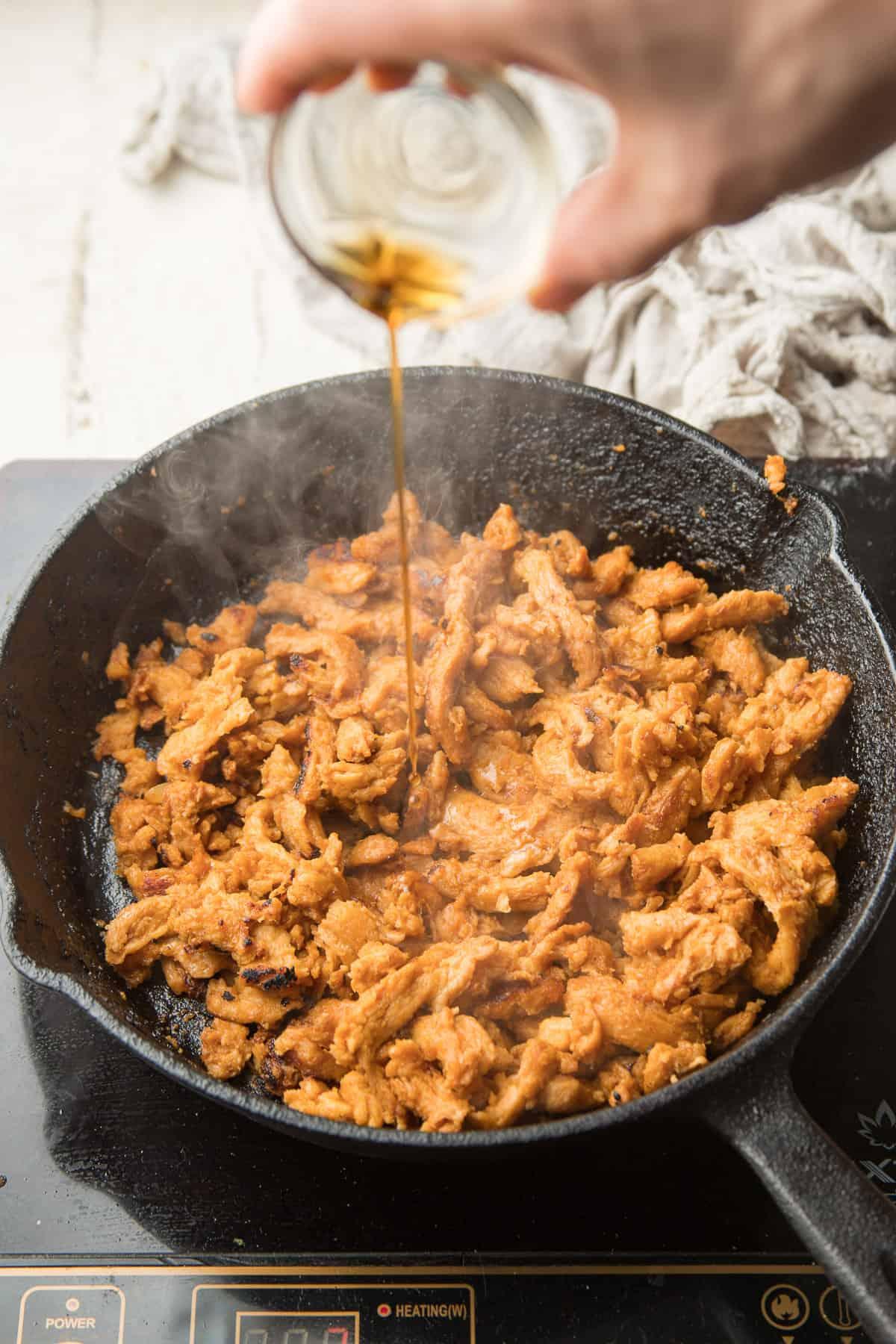 Hand Pouring Sesame Oil into a Skillet of Vegan Bulgogi.