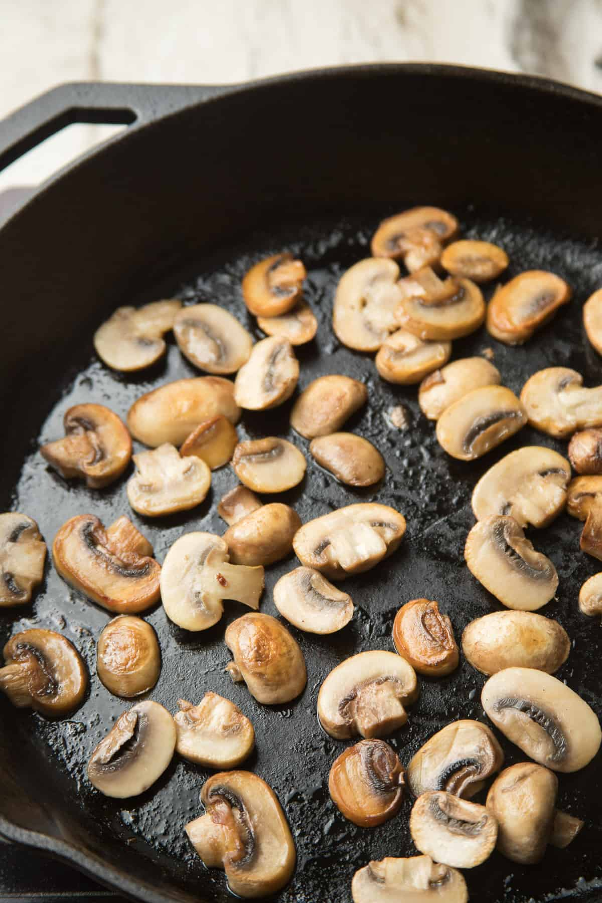 Mushrooms sizzling in a skillet.