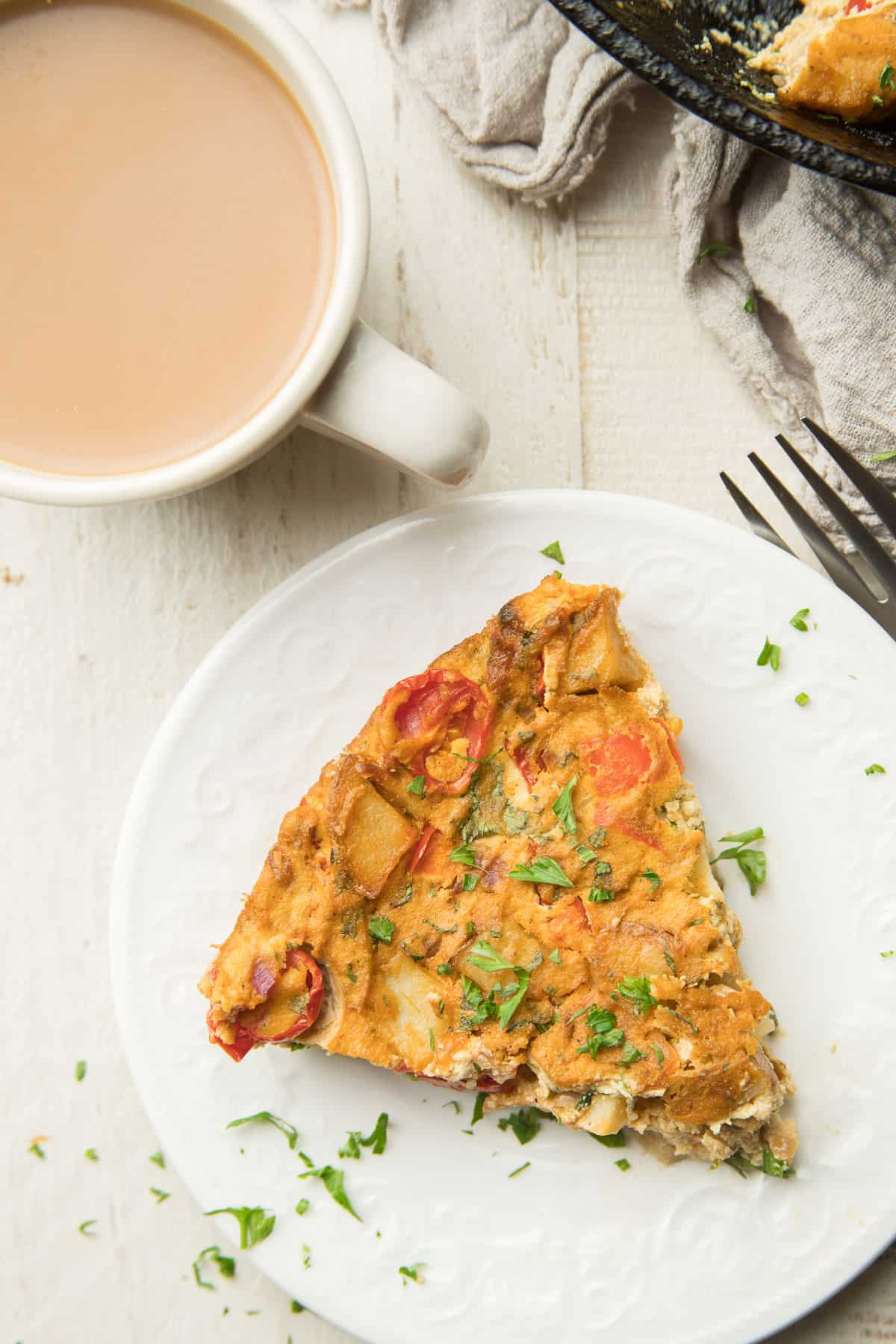 White wooden surface set with skillet, coffee cup, and slice of Vegan Frittata on a plate.