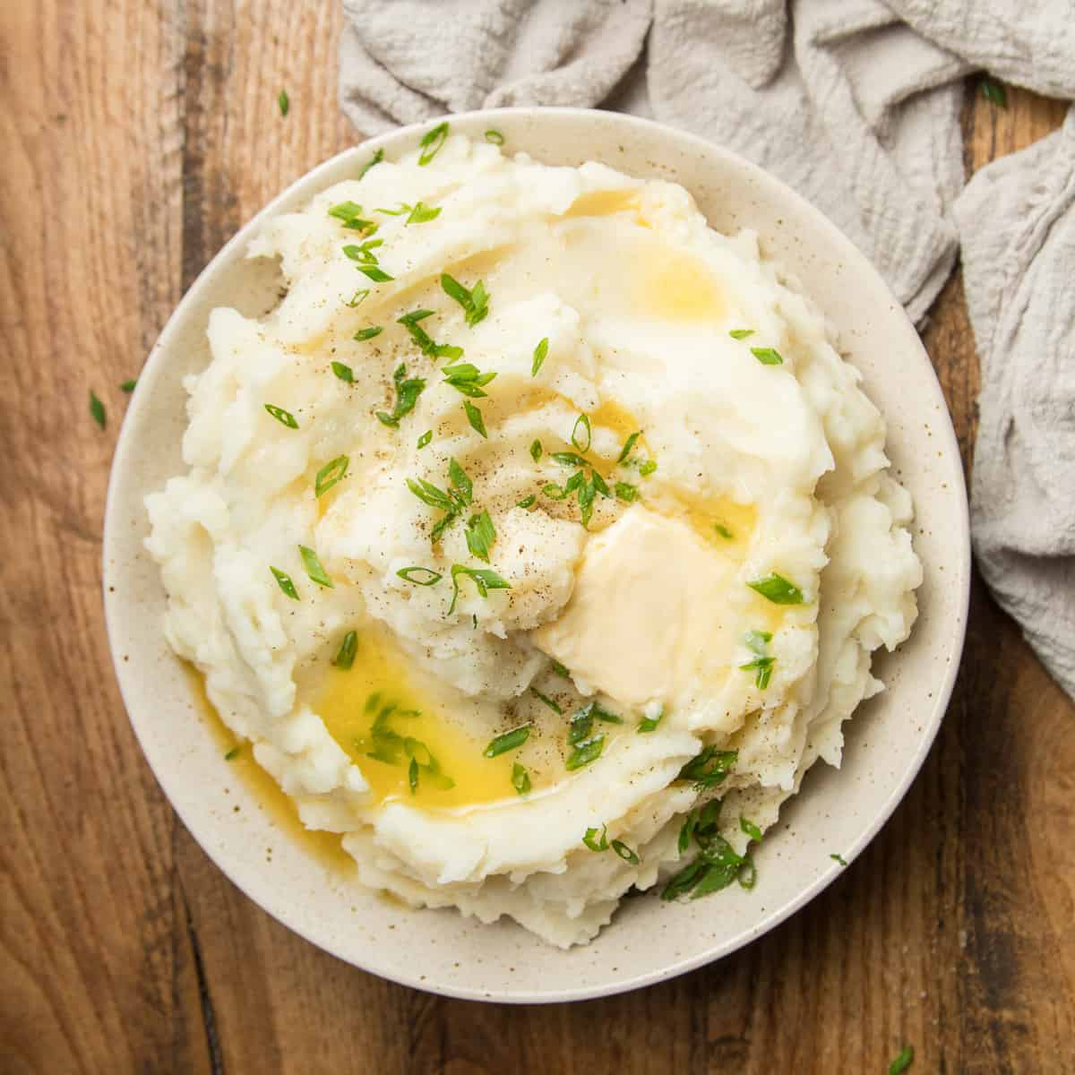 Bowl of Vegan Mashed Potatoes Topped with Butter and Chives.