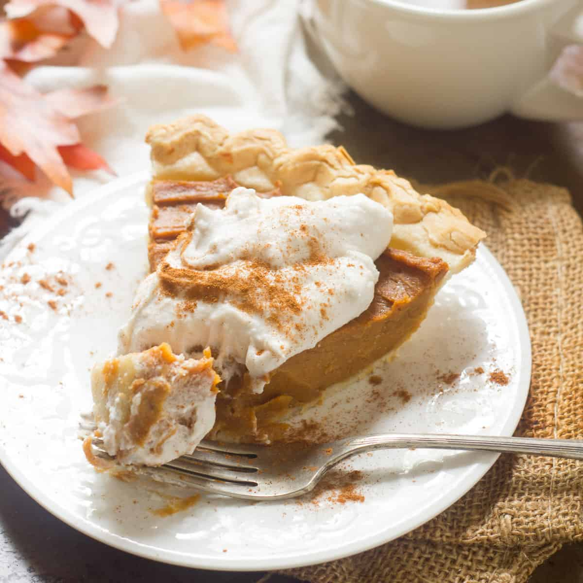 Slice of Vegan Sweet Potato Pie with Whipped Coconut Cream on Top and Fork.