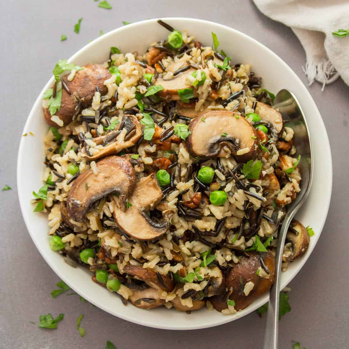 A Bowl of Wild Rice Pilaf with Mushrooms and Pecans with Serving Spoon