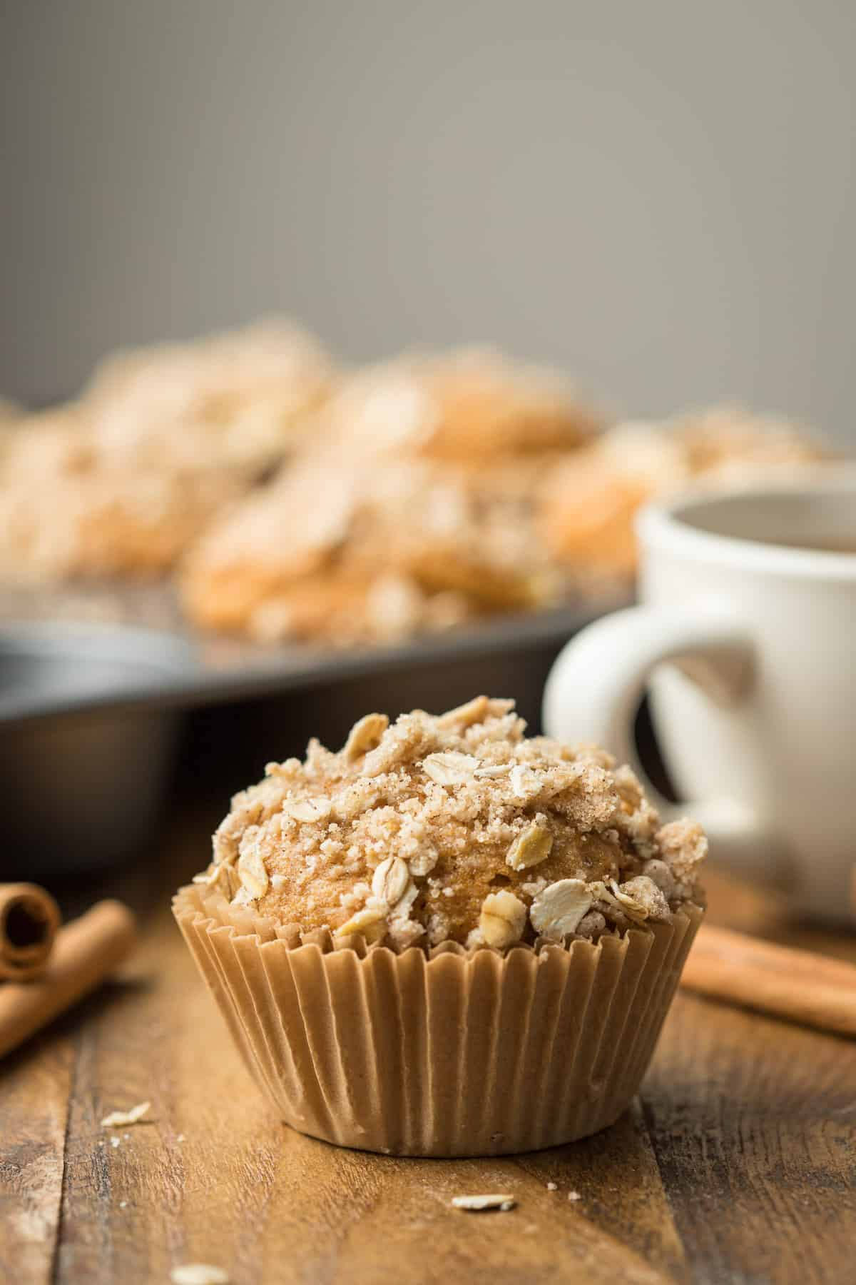 Vegan Pumpkin Muffin with coffee cup and muffin tin in the background.