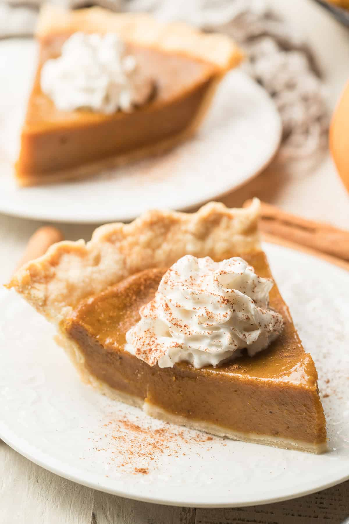 Two plates with slices of Vegan Pumpkin Pie and whipped topping.
